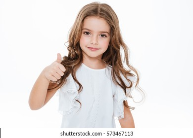 Happy cute little girl standing and showing thumbs up over white background