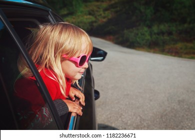 happy cute little girl travel by car in nature