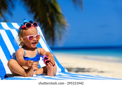 happy cute little girl trying on sunglasses at the beach