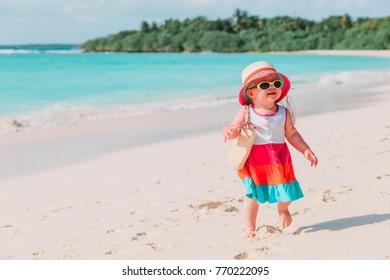 happy cute little girl walk on sand beach
