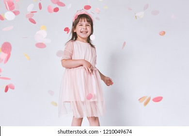 Happy cute little girl wearing pink dress in tulle with princess crown on head isolated on white background playing with confetti. Celebrating brightful carnival for kids, birthday party, having fun