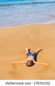 Happy cute little kid laying on the warm sand on tropical beach in Hawaii