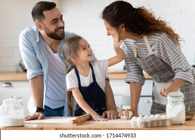 Happy cute little preschool girl spreading flour on cheerful parents. Laughing married couple having fun with small adorable kid daughter, playing together at free time, enjoying family activity.