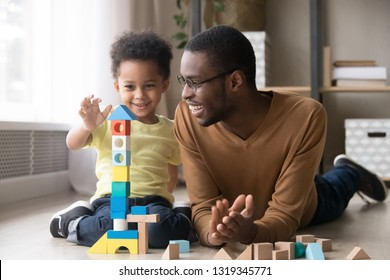 Happy cute little son playing game with black dad baby sitter building constructor tower from multicolored wooden blocks, african family father and toddler child boy having fun on warm floor at home - Shutterstock ID 1319345771