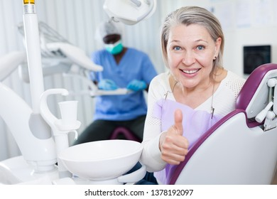 Happy cute mature woman sitting in dental chair after teeth cure giving thumb up
