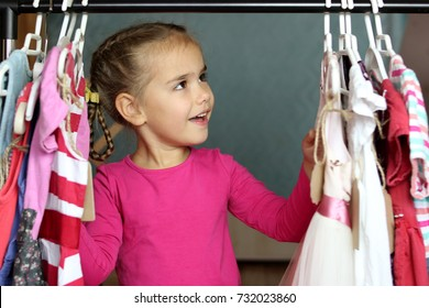 Happy cute preschooler girl choosing a new dress among a lot of clothes in the child fashion store; she is surprised. Sale, gifts, Christmas, holidays; beauty and fashion concept. Indoor portrait