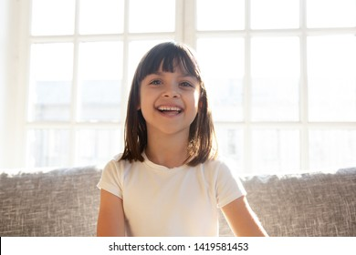 Happy cute preschooler girl sit on couch talking on web cam  conversation, funny little child vlogger shoot vlog speak chat with subscribers, smiling small kid record video on sofa at home
