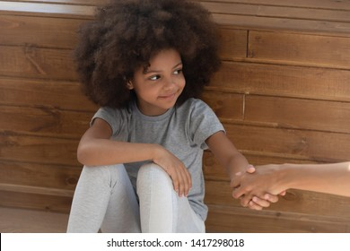 Happy cute small kid girl orphan holding hand of foster care mom sit on floor, smiling little adopted child find new family, charity concept, parent children protection, adoption, hope and donation
