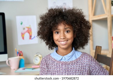 Happy cute smiling African American black preteen girl with curly afro hairstyle posing indoors in room looking at camera. Headshot closeup portrait of mixed race model.