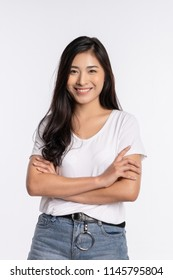 Happy cute smiling beautiful young Thai Asian woman crossing arms showing ok sign gesture, she wearing white t shirt, isolated over white background, - success concept for advertising