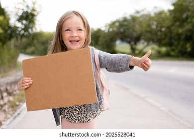 Happy cute smiling child girl 3-4 year old hold paper craft blank board making thumb up hitch hiking on road outdoors. Happiness. Little kid toddler travel wear casual clothes and backpack. Childhood.