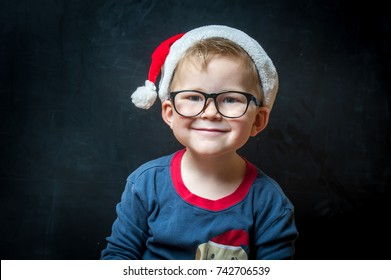 Happy cute smilling boy in red xmas hat so happy about it. Funny smiling child in glasses waiting for Christmas magic.