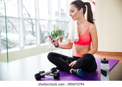 Happy cute sportswoman in earphones listening to music and using smartphone in gym