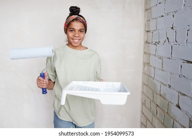 Happy cute teenage girl with paintroller and white square plastic container with paint standing in the corner by two walls of living-room