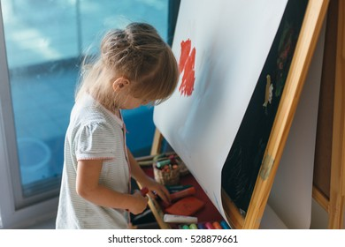 Happy cute toddler girl painting with gouache and watercolor paints on the easel indoors