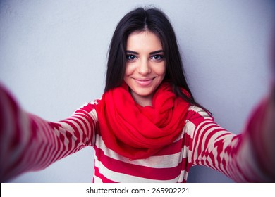 Happy cute woman making selfie over gray background. Wearing in bright scarf and sweater. Looking at camera