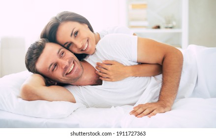 Happy cute young beautiful couple in love hugging each other and having fun in the big white bed after dream