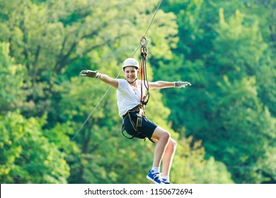 Happy, cute, young boy in white t shirt and helmet having fun and playing at adventure park, flying on the ropes.  Hobby, active lifestyle concept
