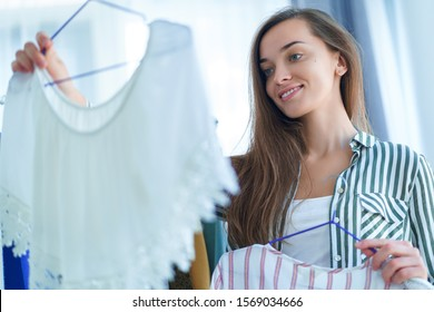 Happy cute young brunette woman standing near wardrobe closet rack full of stylish trendy clothes on hangers at showroom and choosing outfit