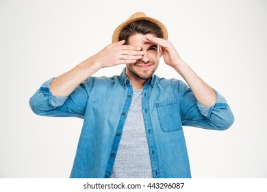 Happy cute young man covered one eye with hand and smiling over white background