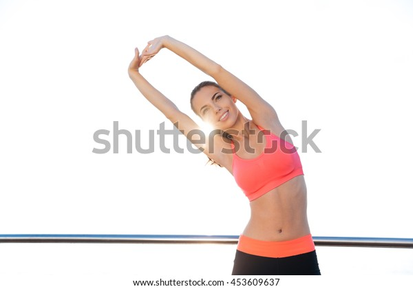 Happy cute young woman athlete smiling and stretching outdoors in the morning