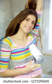 Happy cute young woman drying long hair