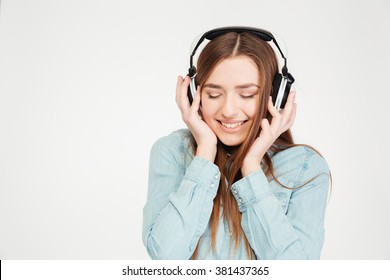 Happy cute young woman in earphones listening to musinc with closed eyes over white background
