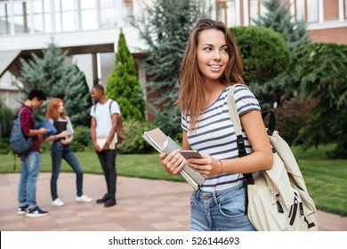 Happy cute young woman student with backpack holding books and walking outdoors