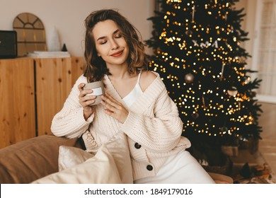 Happy cute young woman in a warm cardigan relaxes celebrates Christmas with a Cup of coffee sitting on the sofa by the decorated Christmas tree in the living room in a cozy home
