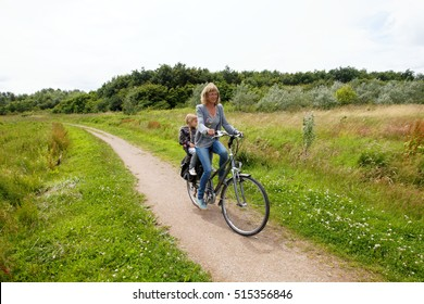 happy cyclist on bike in nature with child behind bicycle