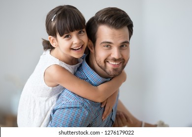 Happy dad carrying little cute child girl on back giving kid piggyback ride having fun together, smiling single father playing with daughter embracing daddy laughing looking at camera, portrait