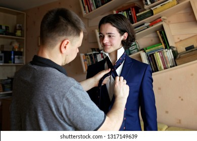 Happy dad helps his student son in business suit to knot necktie at home, family care, education and first job, lifestyle indoor portrait