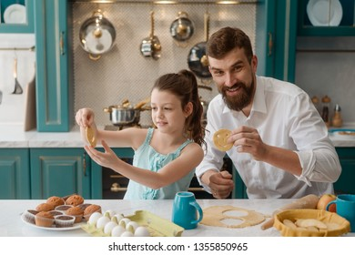 Happy dad with his daughter cut out smile cookies in the kitchen. Preparing desserts for a party. Find time for kids concept.