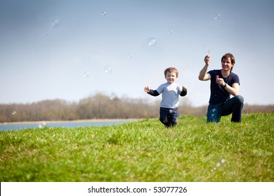 happy dad and his son playing together in the nature with soap bubbles