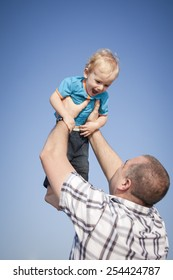 Happy dad holding young son up against blue sky