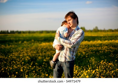 happy dad keeping his tired son in his arms in the field of dandelions