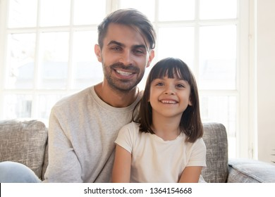 Happy dad kid at home, father sitting on sofa with little daughter smiling looking at camera use laptop web cam make video call record new family vlog. Modern tech and communications online concept