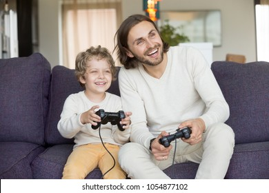 Happy dad laughing playing video game with excited son at home, smiling father having fun with kid boy holding joysticks, child gamer enjoying videogame spending time with daddy together on weekend