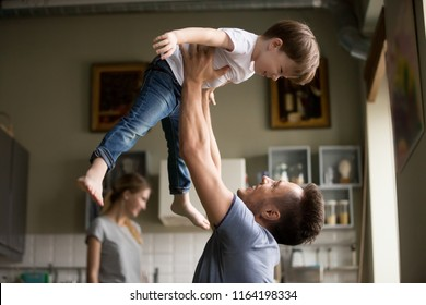 Happy dad lifting son up having fun together at home, young loving father and little child playing funny game in living room, daddy laughing enjoying spending time with kid boy and family on weekend