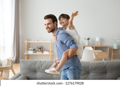 Happy dad piggybacking little funny daughter playing with daddy at home, cheerful single parent carrying kid on back having fun together, child girl enjoying active game with father in living room