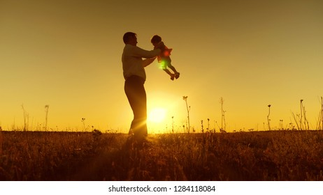 happy dad playing with little daughter, dad circling small child at sunset, Slow motion