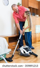 Happy dad and small daughter hoovering apartment together