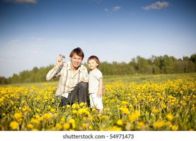 happy dad and son launch paper plane in the field of dandelions