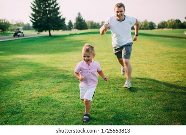 happy dad and son play and run in the summer park