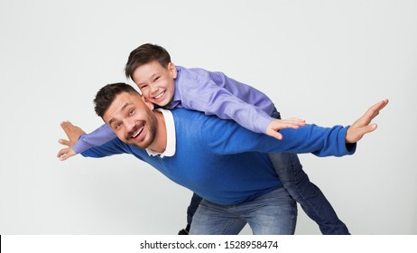 Happy dad and son playing together, man riding boy on back like flying on plane, white panorama background