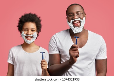 Happy dad and son with pleasant appearance, have shaving foam on faces, hold razors and going to shave, stand in frot of mirror in pink bathroom, have fun together. African kid imitates father