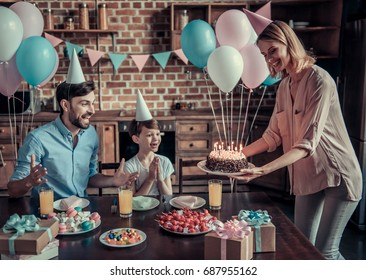 Happy dad and son are sitting at the table in decorated kitchen during birthday celebration, mom is holding a birthday cake
