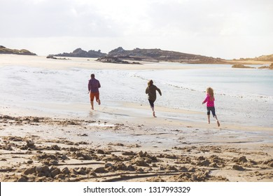 happy dad and two daughters running along the beach at low tide. typical Brittany coast at  the Tregastel in the north of France