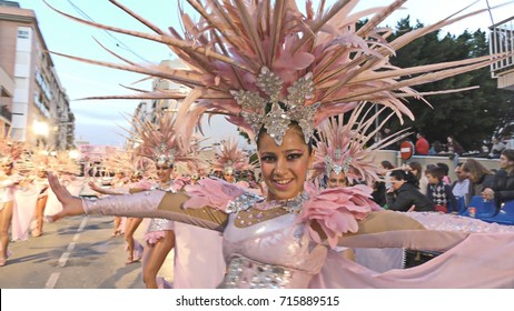 Happy dancers dressed pink parade during Carnival of Aguilas with costumes and feathers. A party with international tourist interest. Aguilas, Spain, February 28, 2017.