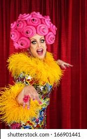 Happy dancing drag queen in pink foam wig